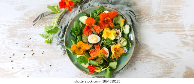 flat lay plate of salad with eggs, cucumbers and edible nasturtium flowers on light wooden table, space for text