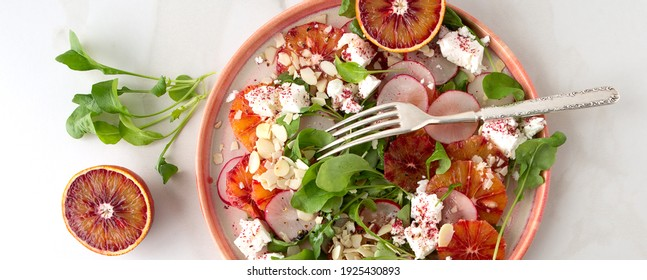 flat lay plate of salad with oranges,feta, arugula and radishes on light marble table