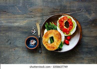 Flat lay of plate with veggie sandwiches. Avocado, soft cheese, tomatoes and aspargus on bagels over wooden background. Top view. Weight loss, clean eating, detox food concept