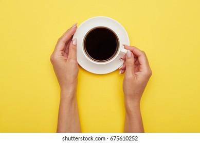 Flat lay of porcelain mug of espresso in girl hands