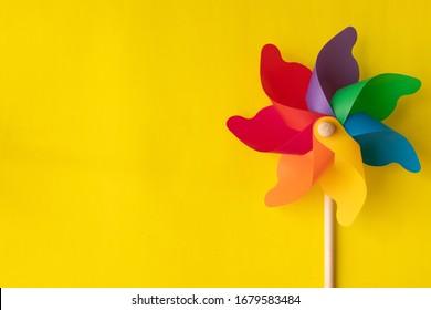 Flat lay Rainbow pinwheel on yellow background, copy space.