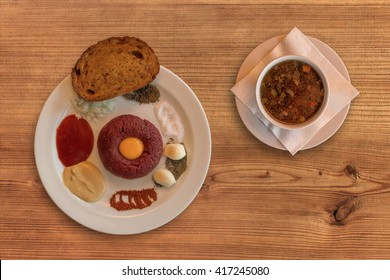 Flat lay of raw beef. Steak tartare. Steak tartare on rustic wooden table with a beef broth. Raw beef meat, salt, pepper, onion, caraway, mustard, tomato pyre, egg, garlic, toast or fried bread.