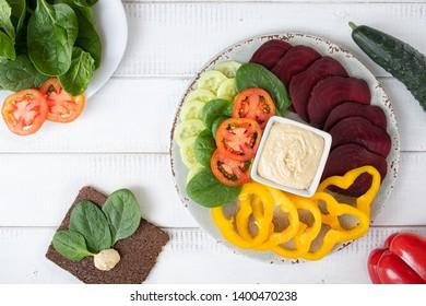 Flat lay of raw vegan food and hummus.