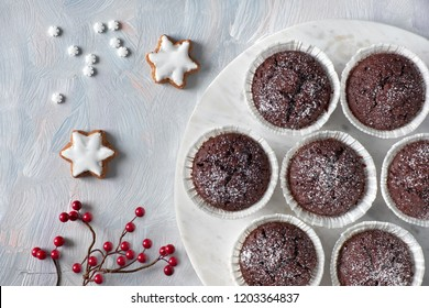 Flat lay with red berry decoration on white rustic background and chocolate muffins in white paper cups with sugar icing on white marmor board