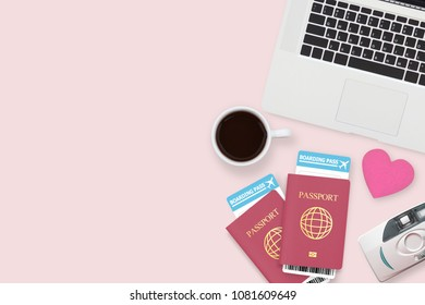 flat lay of red heart on two passport , coffee , computer laptop and copy space on pink pastel background. travel , honeymoon and vacation concept