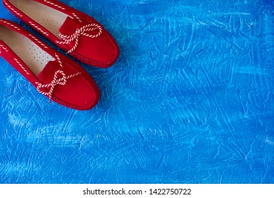Flat lay red loafers on blue background. Summer fashion concept with copy space. Sailor style.