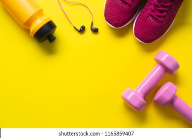Flat lay of red sport shoes, pink dumbbells, earphones, bottle of water on yellow  background. Active Healthy lifestyle, working out, weight and dieting concept.