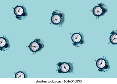 Flat lay retro beautiful new alarm clock on blue color background. Pattern. Top view