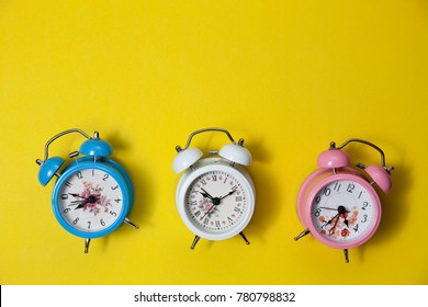 Flat lay retro beautiful new alarm clock on yellow paper pastel color background.