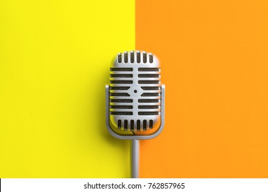 Flat lay of retro microphone on double colorful background.
