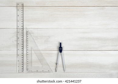 Flat lay of riangle centimeter ruler, simple centimeter ruler and engineering divider on wooden surface. Top view composition. Working stuff. Work place of draftsman, architect, constructor