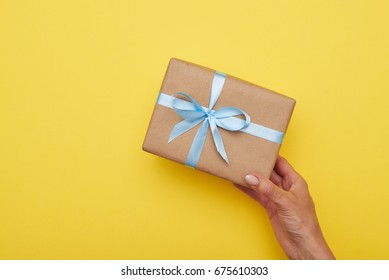 Flat lay of romantic present decorated with bow in woman hand
