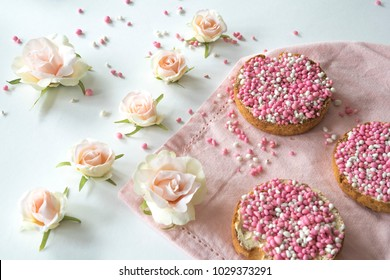 flat lay roses pink, napkin with crispy rusk with traditional Dutch food muisjes, aniseed, announcement that a baby girl is born. white background.
