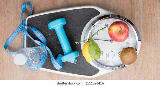 flat lay scale weighs person with water bottle fruit dumbbells and a meter symbol of good hygiene of life to lose weight in top view