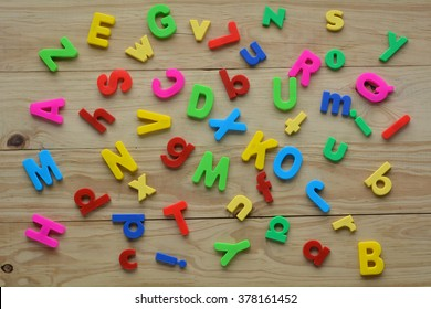 Flat lay of scattered English letters on a wooden background. Language education concept