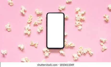 Flat lay scattered popcorn with mobile phone with blank screen on pink background. Mockup phone with white copy space. Smartphone application for online cinema, films and media.  - Shutterstock ID 1810611049