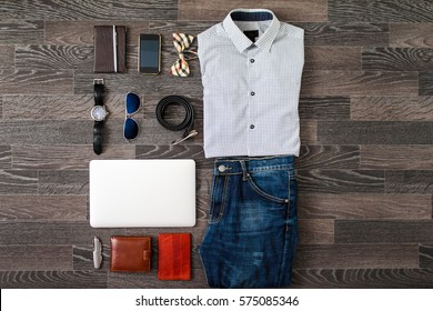 Flat lay set of casual men`s clothes and accessories on dark black wooden background. Top view.
