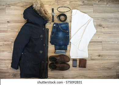 Flat lay set of casual winter men`s clothes such as jacket with fur and accessories on brown wooden background. Top view.