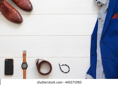 Flat lay set of classic men`s clothes such as blue suit, brown shoes, belt, watches ,leather cell phone and bracelet on white wooden background. Top view.