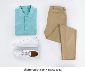 Flat lay set of classic men`s clothes such as polo, sandy trousers and white shoes on white background. Top view.