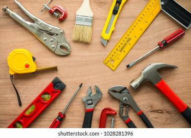 Flat lay, set of construction hardware tools building, repair, painting accessories on wooden board background