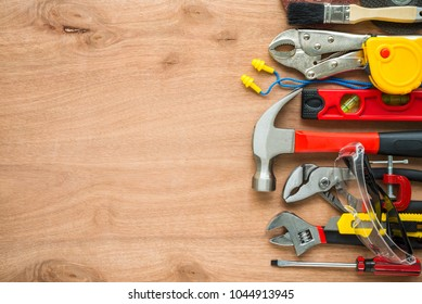 Flat lay, set of construction hardware tools building, repair, painting accessories on wooden board background with copy space