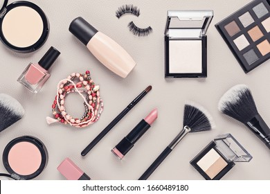 Flat lay with set of professional decorative cosmetics, makeup tools and woman accessories over gray background with copy space. Beauty blog, fashion, party and shopping concept. Top view