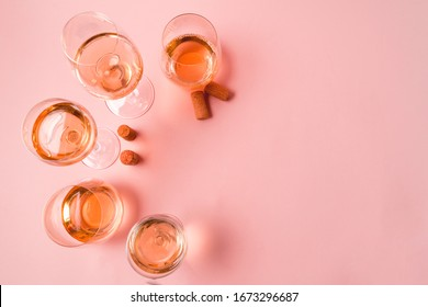 Flat lay. A set of rose and white wine in a glasses on pink background, toned in pink, copy space.