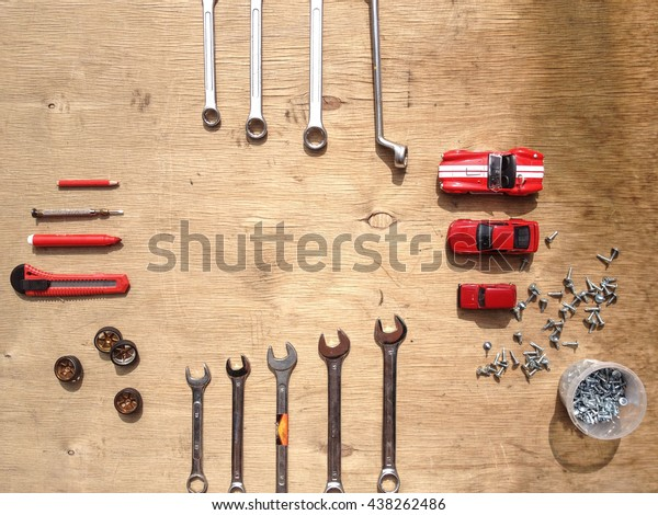 Flat lay of set of tools for car repairing such as wrenches on wooden background with contrast red toy cars. Top view.