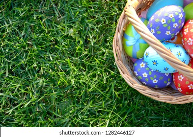 Flat lay shot of Easter eggs in the wicker basket on green spring grass