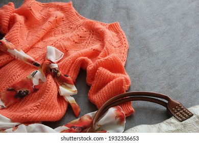 Flat Lay Shot Of Female Spring Clothing And Accessories. Pink Sweater, Ddress, Handbag On Grey Backgound .