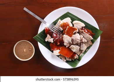 Flat Lay shot of [lechon or suckling pig chopped parts serve with banana leaf. The food is popular in Spain and former Spanish colonial regions.