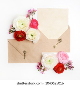 Flat lay shot of letter and eco paper envelope on white background. Wedding invitation cards or love letter with ranunculus flowers. Valentine's day or other holiday concept. Top view