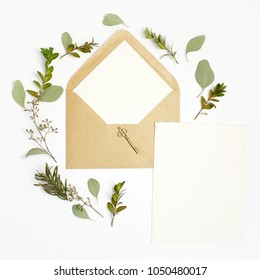 Flat lay shot of letter and eco paper envelope on white background. Wedding invitation cards or love letter with plant. Valentine's day or other holiday concept. Top view