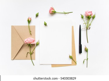Flat lay shot of letter and eco paper envelope on white background. Wedding invitation cards or love letter with pink roses. Valentine's day or other holiday concept, top view, flat lay, overhead view