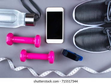 Flat lay shot of sneakers, earphones and phone on gray background with copy space for your text. Smartphone mockup.