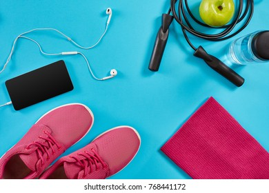 Flat lay shot of sneakers, jumping rope, dumbbells and smartphone on blue background.