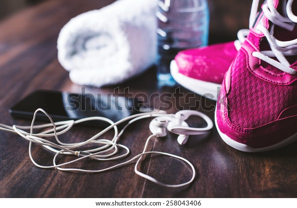 Flat lay shot of Sport equipment. Sneakers, water, towel, earphones and phone on wooden background. Focus is only on the sneakers.