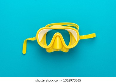 flat lay shot of yellow diving mask over turquoise blue background. minimalist photo of dive mask with central composition