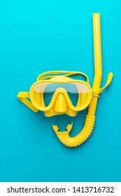 flat lay shot of yellow diving mask with snorkel over blue background. minimal conceptual photo of dive mask and snorkel central composition. flat lay of diving equipment vertical orientation