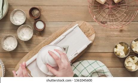 Flat lay. Slicing organic gold potatoes on a V-blade mandoline to prepare scalloped potatoes. - Shutterstock ID 1361045600