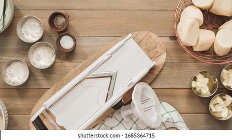 Flat lay. Slicing organic gold potatoes on a V-blade mandoline to prepare scalloped potatoes. - Shutterstock ID 1685364715
