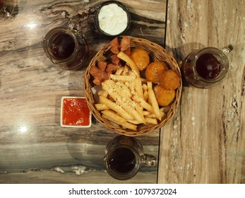 flat lay snack consists of french fries, fried sausages, bitterballen with mayonaise and tomato or chili sauce accompanied by coffee