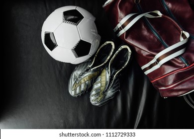 Flat lay soccer football ball and boots accessories on a dark leather background. Mock-up with copy space for text. and a leather sports bag. Top view.