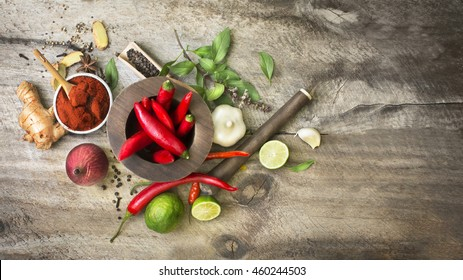 Flat lay south east asian cuisine recipe herbs, spices and other ingredients with wooden traditional food grinder on rustic wooden background. Horizontal view text space images.