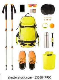 Flat lay of sport equipment and gear for hiking and trekking. Top view of walking poles, backpack, food, boots, etc. isolated on white background