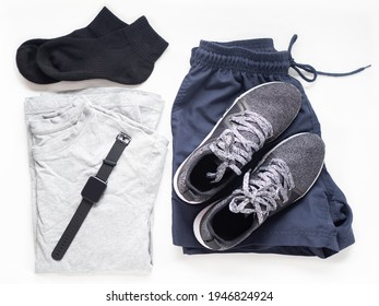 Flat lay of sport outfit for run or workout dark color set (black sneaker, black socks, dark blue short, grey shirt, gps tracking watch)