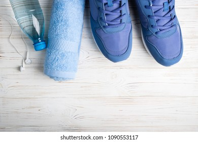Flat lay sport shoes, bottle of water, towel and earphones on white background. Sport equipment. Healthy lifestyle, sport and diet concept. Copy space, top view