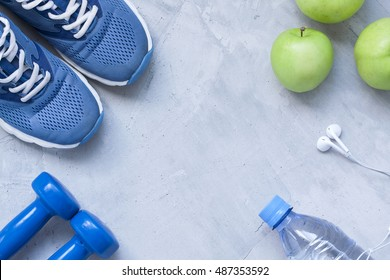 Flat lay sport shoes, dumbbells, earphones, apples, bottle of water on gray concrete background. Concept healthy lifestyle, sport and diet. Selective focus. Flat lay shot of Sport equipment.