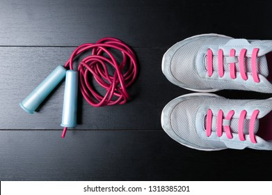 flat lay sports accessories sneakers with jump rope on black